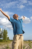 Carefree man enjoying life, stretching his arms to the sky and r Stock Image