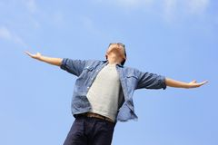 Carefree man. Carefree and free man raised hands and looking to a sky, asian Stock Image