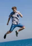 Carefree man jumping by sea ocean. Happy guy having fun. Summer happiness and freedom Stock Photos