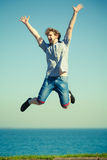 Carefree man jumping by sea ocean water. Stock Images