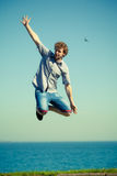 Carefree man jumping by sea ocean water. Royalty Free Stock Photo