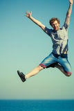 Carefree man jumping by sea ocean water. Stock Photos