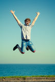Carefree man jumping by sea ocean water. Royalty Free Stock Photography