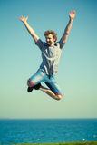 Carefree man jumping by sea ocean water. Royalty Free Stock Images