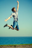 Carefree man jumping by sea ocean water. Royalty Free Stock Photos