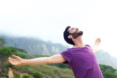 Carefree man smiling with arms open. Portrait of a happy carefree man smiling with arms open outdoors Royalty Free Stock Photos