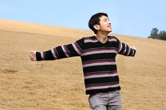 Carefree man standing in golden grass field. Being happy enjoying freetime Royalty Free Stock Image