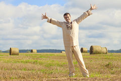 Carefree man standing in golden wheat. Field being happy enjoying freetime Stock Image
