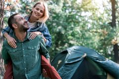 Carefree married couple having fun in forest. Spending great time in the nature together. Portrait of joyful men holding his wife on back and laughing. Woman is Royalty Free Stock Image