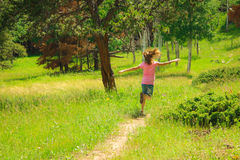 Carefree in Meadow. A girl running carefree along a dirt path through a natural green field Royalty Free Stock Photos