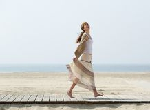 Carefree middle aged woman walking barefoot. Full length portrait of a carefree middle aged woman walking barefoot at the beach stock image