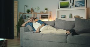 Carefree middle eastern guy watching tv laughing lying on couch in dark house. Carefree middle eastern guy is watching tv laughing lying on couch in dark house stock footage
