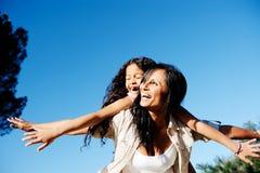 Carefree moder och barn som leker i sunen arkivfoto