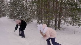 Carefree mom and daughter playing to snow fight in winter forest slow motion stock video