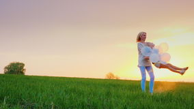 Carefree mom plays with her daughter in a picturesque place - on a large green meadow with a lonely tree on the horizon stock video