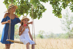 Carefree mother playing with her daughter. Joyful women is pushing swing with her daughter. She is standing on meadow and smiling. Child is sitting and holding Royalty Free Stock Images