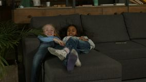 Two multiracial little girls playing on the couch. Carefree multi etnic preteen girlfriends playing on the couch and having fun while enjoying freetime together stock footage