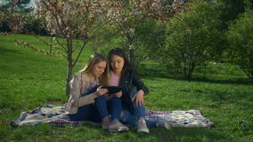 Carefree multiethnic women with tablet pc on park lawn stock video footage