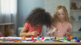 Carefree multiracial female kids sitting at the table and painting, art hobby. Stock footage stock video