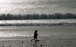 Carefree Ocean Romp. A girl romps on the beach in Ventura, California royalty free stock images