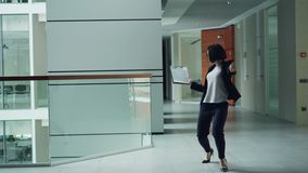 Carefree office worker is dancing in lobby holding paper then throwing folder away and relaxing moving body. Modern