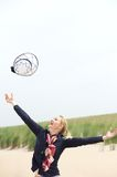 Carefree older woman throwing hat up with outstretched arms stock photography