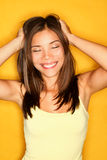 Carefree playful young woman. Touching her hair smiling happy on yellow background. Pretty joyful mixed race Caucasian / Asian woman Stock Images