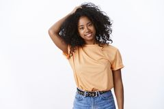 Carefree pleased attractive young body-positive dark-skinned girl touching curls afro hairstyle tilting head happily stock photo