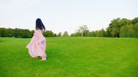 Carefree pregnant woman in a light pink dress. Walking through the green meadow stock video