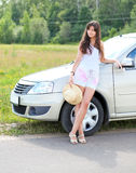 Carefree pretty girl relaxing. Near light car in countryside Stock Photography