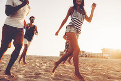 Carefree run. Group of young cheerful people running along the beach and looking happy Stock Image
