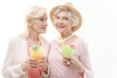 Carefree senior female friends drinking cocktails. Waist up portrait of two pretty old ladies enjoying their vacation. They are tasting exotic beverage and Royalty Free Stock Photo