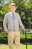 Carefree senior gentleman with a cane posing in park Royalty Free Stock Photography