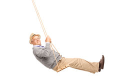 Carefree senior man swinging on a wooden swing. And looking at the camera isolated on white background Royalty Free Stock Photo