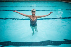 Carefree senior woman swimming in pool Stock Images