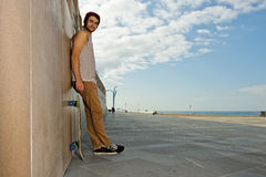 Carefree skateboarder. Young, carefree, skateboarder guy, leaning against a granite wall at a beach with his skateboard next to him Stock Image