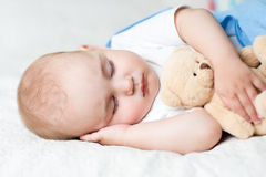 Carefree sleep baby with soft toy. On bed royalty free stock photo