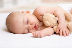 Carefree sleep baby with soft toy. Carefree sleep baby boy with soft toy on bed Stock Photography