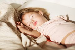 Carefree sleep little baby with a soft toy on the bed. Stock Photos