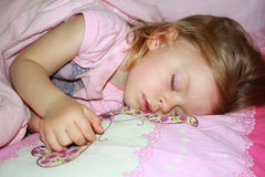 Carefree sleeping little girl. On a bed Stock Image