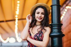 Carefree slim woman with dark luxurious hair, shinig eyes and red rouged lips, dressed in straw hat and dress while posing at cafe royalty free stock photography