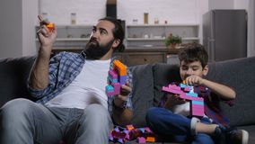 Carefree dad and son playing with building blocks stock video footage