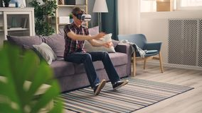 Carefree student is playing game with virtual reality glasses driving car racing sitting on sofa at home and moving. Carefree male student is playing game with stock footage