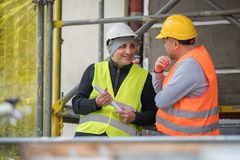 Carefree talking between two civil engineers during work break on construction site. Outdoors Royalty Free Stock Image