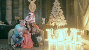Carefree Teen friends Celebrate Christmas near Decorated Christmas looking at a new application in smartphone. Slowmotion stock video footage