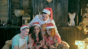 Carefree Teen friends Celebrate Christmas near Decorated Christmas watching videos smartphone. Slow motion stock video footage
