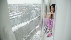 Carefree leisure bored teen girl sit windowsill. Carefree teenage leisure. bored young girl sitting on the windowsill and looking out of the window stock video footage