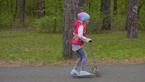 Carefree teenager girl riding a scooter on road in green spring city park stock footage
