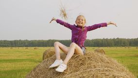 Carefree teenager girl scattering dry straw on countryside field. Happy girl teenager sitting on hay stack. Young girl stock video
