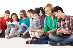 Carefree teenagers. Group of multi-ethnic students spending time together while sitting isolated on white Stock Images